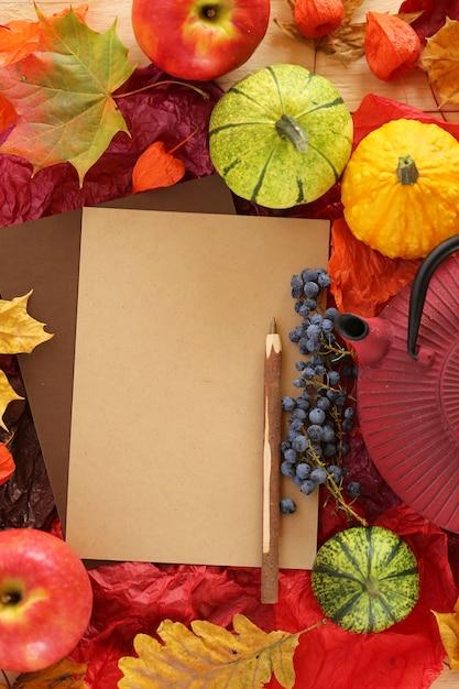 木製のペン、メープルの明るい葉、リンゴ、小さなカボチャと空白の空のカード Premium写真