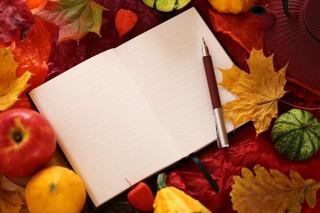 Пустая тетрадь с кленовым листом, яблоками и тыквами Premium Фотографии