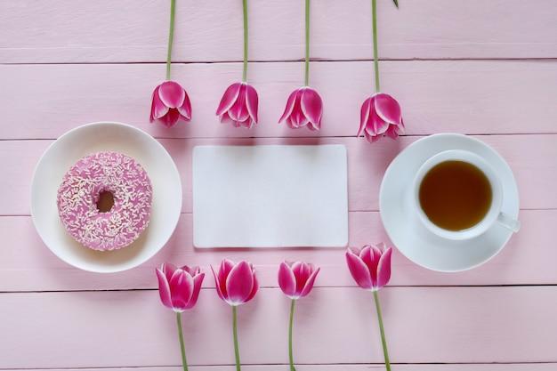 Розовые тюльпаны цветы, пустой блокнот, чашка чая и розовый пончик на розовом деревянном фоне Premium Фотографии