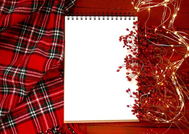空の空白のノートブック、赤い果実、赤い市松模様のスカーフ、輝く花輪の枝 Premium写真