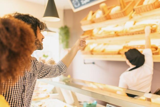 ベーカリーで若いモダンカップル、パンを選ぶ Premium写真