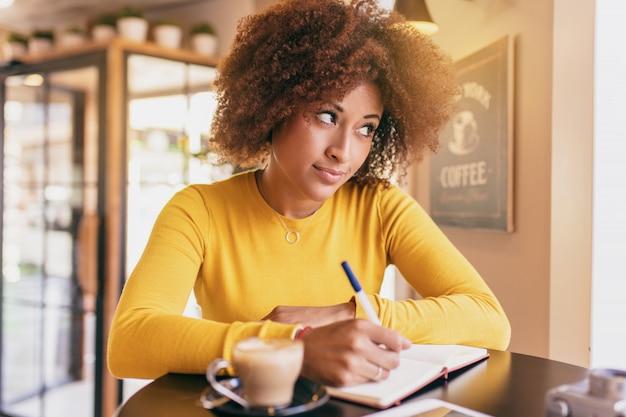 カフェで若いアフロの女性、彼女は書くアイデアを考えている。 Premium写真