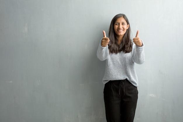 陽気で興奮して、笑みを浮かべて、彼女の木を上げるグランジ壁に対して若いインド人女性 Premium写真