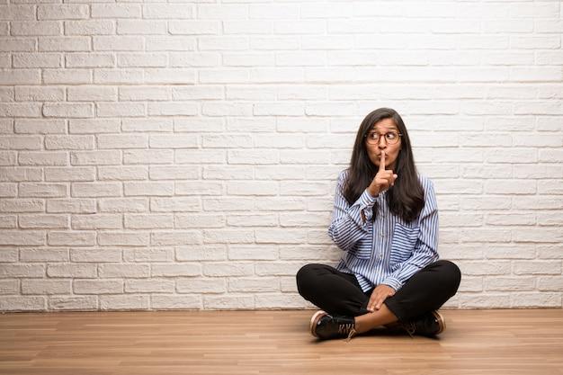 若いインド人女性は、秘密を守るか沈黙を求めるレンガの壁に座る。 Premium写真