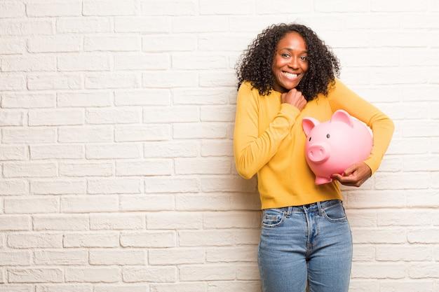 若い黒人女性は非常に幸せで興奮して、腕を上げる、勝利または成功を祝う Premium写真