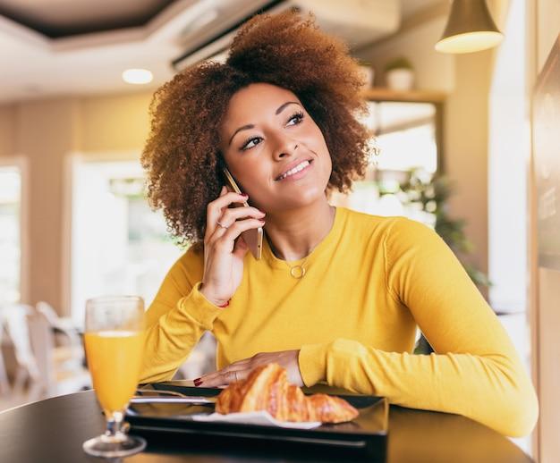 朝食をとり、クロワッサンを食べ、オレンジジュースを飲む若いアフロ女性。 Premium写真