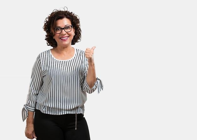 陽気で興奮して、笑顔で彼女の親指を上げる中年の女性 Premium写真