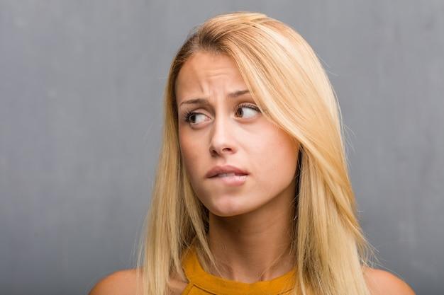 顔のクローズアップ、疑っていると混乱している自然の若いブロンドの女性の肖像画。 Premium写真