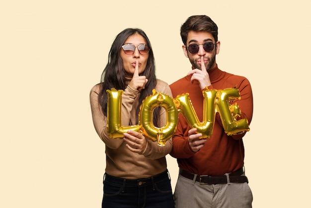 秘密を守るか沈黙を求めるバレンタインデーの若いカップル Premium写真