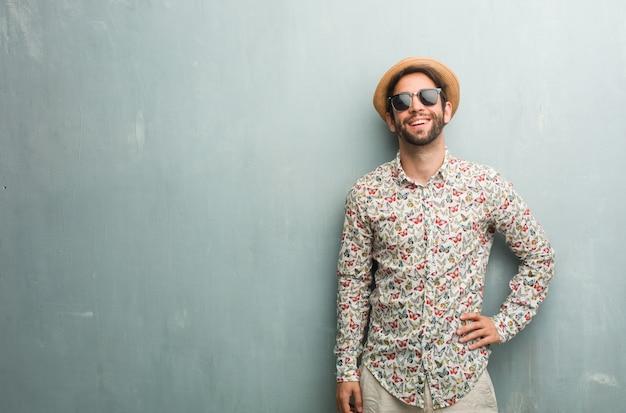若い旅行者の男の腰に手でカラフルなシャツを着て立って、リラックスして笑顔、非常に肯定的で陽気 Premium写真
