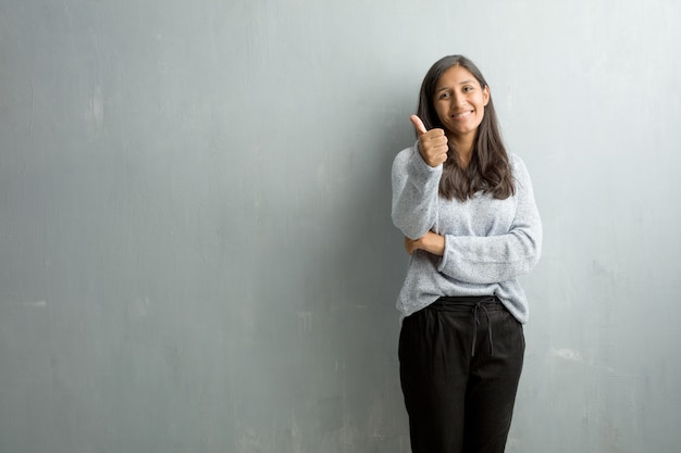 陽気で興奮してグランジの壁に対して若いインド人女性 Premium写真