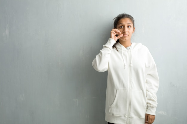 秘密を守るか沈黙、深刻な顔、服従の概念を求めてジムの壁に対してスポーティなインドの若い女性 Premium写真