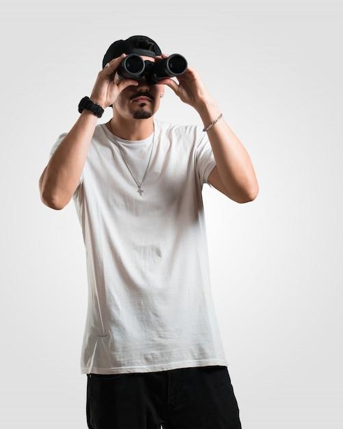 ラッパーの若い男が驚きと驚き、遠くに何か双眼鏡で見て、面白い、将来の機会の概念 Premium写真