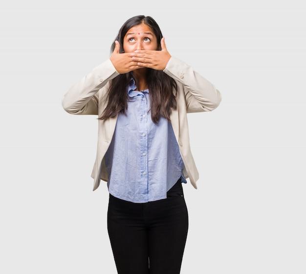 口を覆っている若いビジネスインド人女性 Premium写真