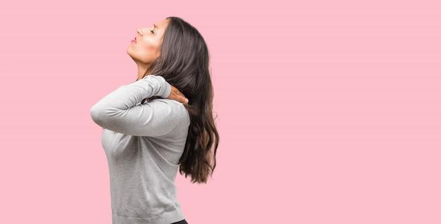 仕事のストレス、疲れて鋭いため背中の痛みを持つ若いインド人女性の肖像画 Premium写真