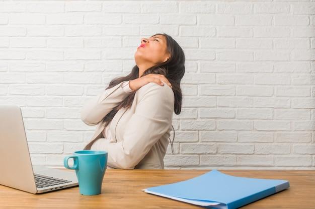 仕事のストレス、疲れて鋭いため背中の痛みを持つオフィスで若いインド人女性 Premium写真
