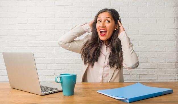 オフィスで若いインド人女性、驚いてショックを受けて、広い目で見て、オファーや新しい仕事に興奮して、概念を獲得 Premium写真