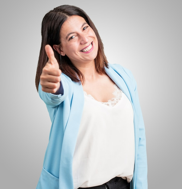 Среднего возраста женщина веселая и взволнованная, улыбается и поднимает большой палец вверх, концепция успеха и одобрения, хорошо жест Premium Фотографии