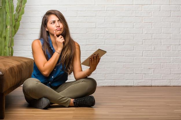 考えて見上げる床に座っている若いラテン女性の肖像画 Premium写真