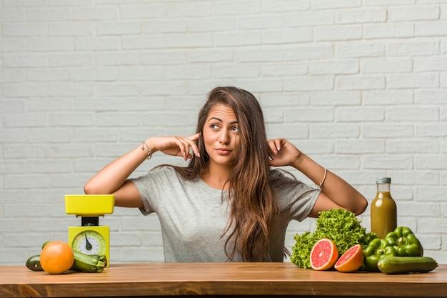 Концепция диеты. портрет здоровой молодой латинской женщины, закрывающей уши руками, злой и усталой от какого-то звука Premium Фотографии