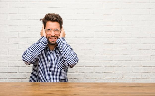 怒っているといくつかの音を聞くのはうんざりして座って手で耳を覆っている若い白人男性 Premium写真
