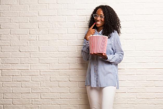 若い黒人女性の笑顔、口を指して、完璧な歯の概念、白い歯は、陽気で陽気な態度をしています Premium写真
