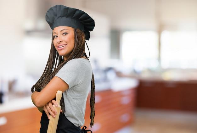 Портрет молодой женщины чернокожего пекаря, скрещивающей руки, улыбающейся и счастливой, уверенной и дружелюбной Premium Фотографии