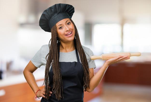 Портрет молодой чернокожей пекари, держащей что-то руками, показывающей продукт, улыбающейся и веселой, предлагающей воображаемый предмет Premium Фотографии