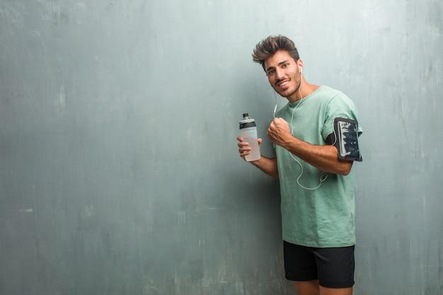 Молодой фитнес человек против стены гранж очень счастлив и взволнован, поднимая руки, празднуя победу или успех, выигрывая в лотерею. носить повязку с телефоном. Premium Фотографии
