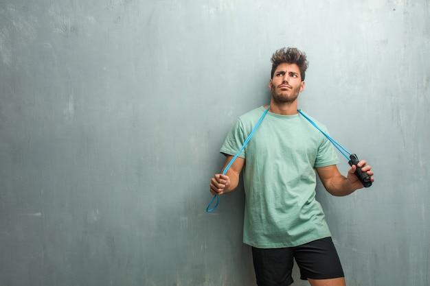 Молодой фитнес человек против гранж стены сумасшедший и отчаянный, кричать из-под контроля, смешные сумасшедшие выражая свободу и дикий. держа скакалку. Premium Фотографии