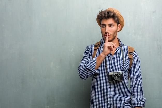 麦わら帽子、バックパック、秘密を守るか沈黙、深刻な顔、服従の概念を求めて写真カメラを身に着けている若いハンサムな旅行者男性 Premium写真