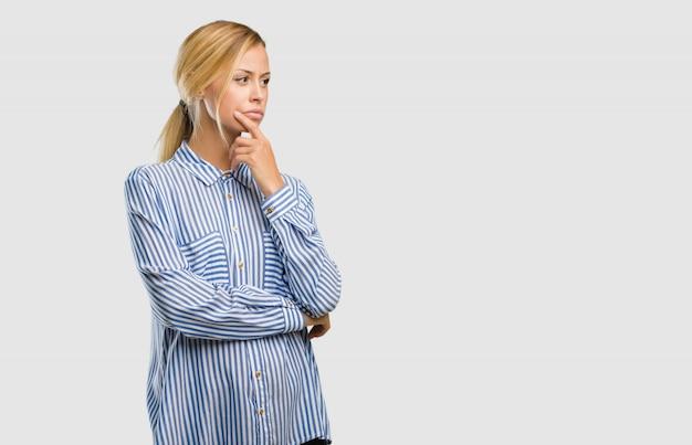 疑問や混乱している、考えを考えている、または何かを心配しているかなり金髪美人の肖像 Premium写真