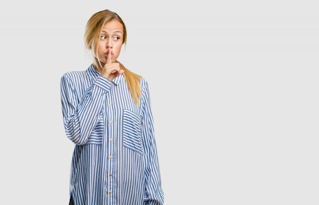 秘密を守るまたは沈黙、深刻な顔、服従の概念を求めてかなり金髪の若い女性の肖像 Premium写真