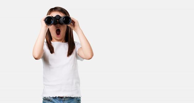 フルボディの女の子が驚きと驚き、遠くに何か双眼鏡で見て何か面白いもの Premium写真