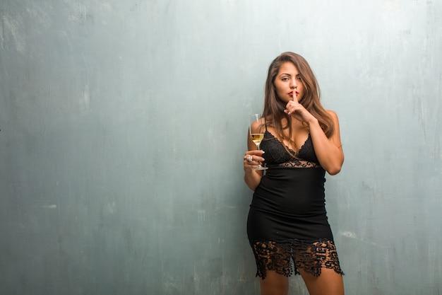 Молодая красивая женщина, одетая в платье у стены, хранящая тайну или просящая молчания Premium Фотографии