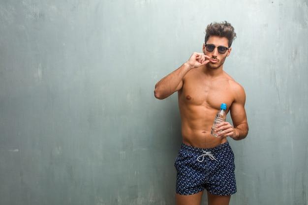 秘密を保持または沈黙を求めてグランジの壁に対して水着を着て運動青年 Premium写真