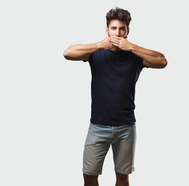 口、沈黙と抑圧の象徴を覆っている立っている若いハンサムな男 Premium写真