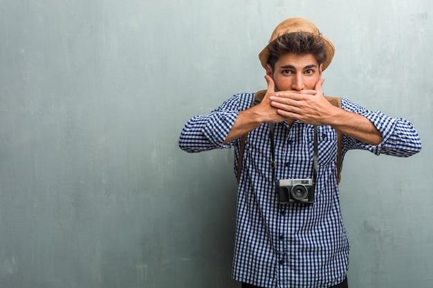 麦わら帽子、バックパック、口を覆っている写真のカメラを身に着けている若いハンサムな旅行者男 Premium写真