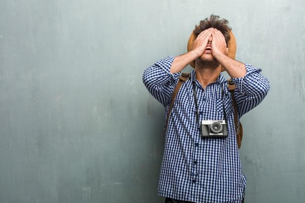 Молодой красивый путешественник человек в соломенной шляпе, рюкзак и фотоаппарат разочарованы и отчаянно Premium Фотографии