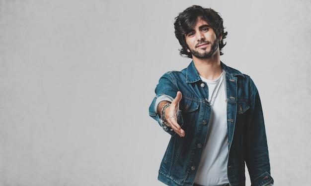 誰かを迎えるために手を差し伸べるか、助けるために身振りで示すこと、幸せで興奮している若いハンサムな男 Premium写真