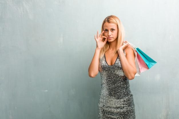 秘密を守るか沈黙を求める若いエレガントな金髪女性の肖像画。買い物袋を持っています。 Premium写真