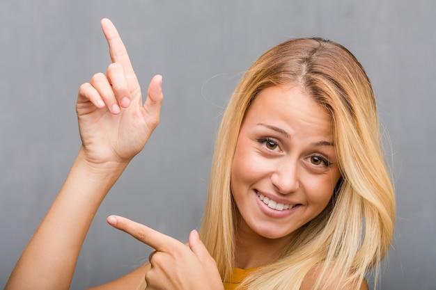 顔のクローズアップ、側を指している自然な若いブロンドの女性の肖像画、 Premium写真