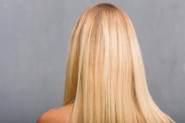 顔のクローズアップ、背中を見せて自然な若いブロンドの女性の肖像画 Premium写真