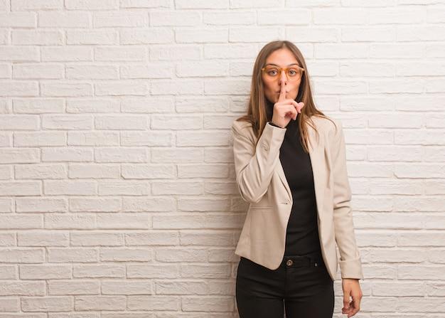 秘密を守るか沈黙を求める若いかなりビジネス起業家女性 Premium写真