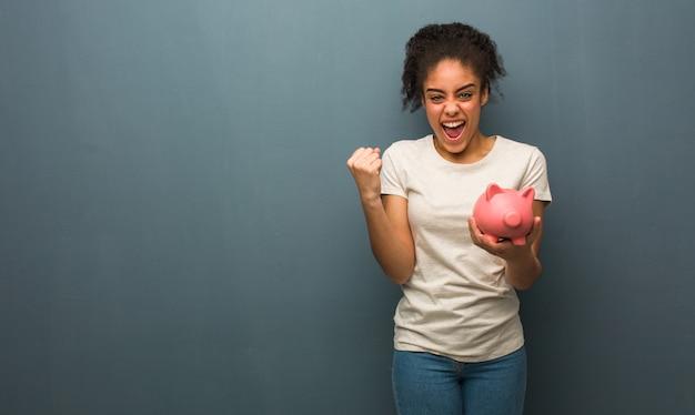 若い黒人女性は驚いてショックを受けました。彼女は貯金を持っています。 Premium写真