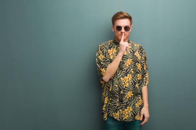 Молодой рыжий мужчина в экзотической летней одежде держит в секрете или просит молчать Premium Фотографии