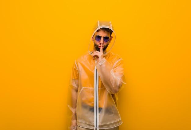 秘密を守るか沈黙を求めるレインコートを着た若い男 Premium写真