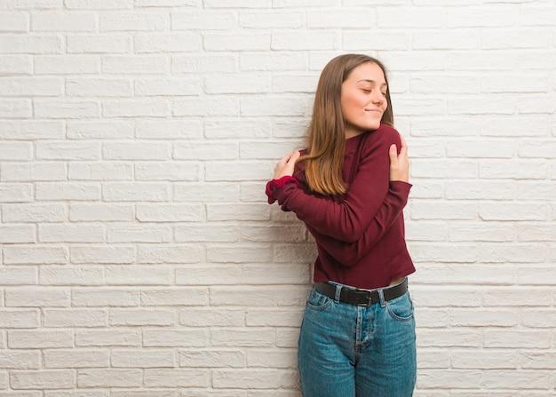 Молодая спокойная женщина над кирпичной стеной Premium Фотографии