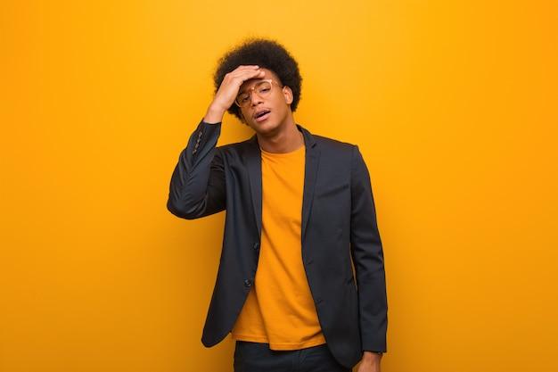 オレンジ色の壁を越えて若いビジネスアフリカ系アメリカ人男性の疲れと非常に眠い Premium写真