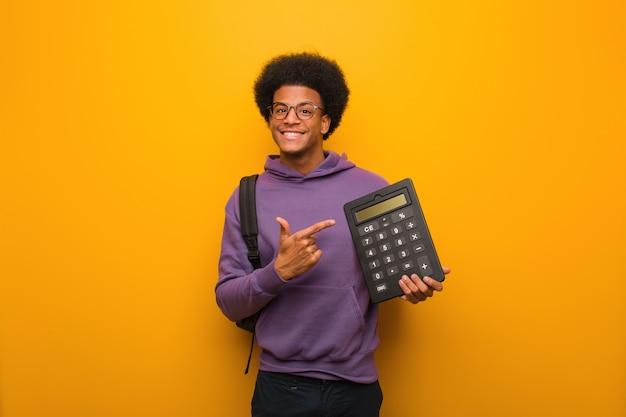 アフリカ系アメリカ人学生の若い男が指で側を指している電卓を保持 Premium写真
